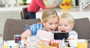 Children playing video games at breakfast